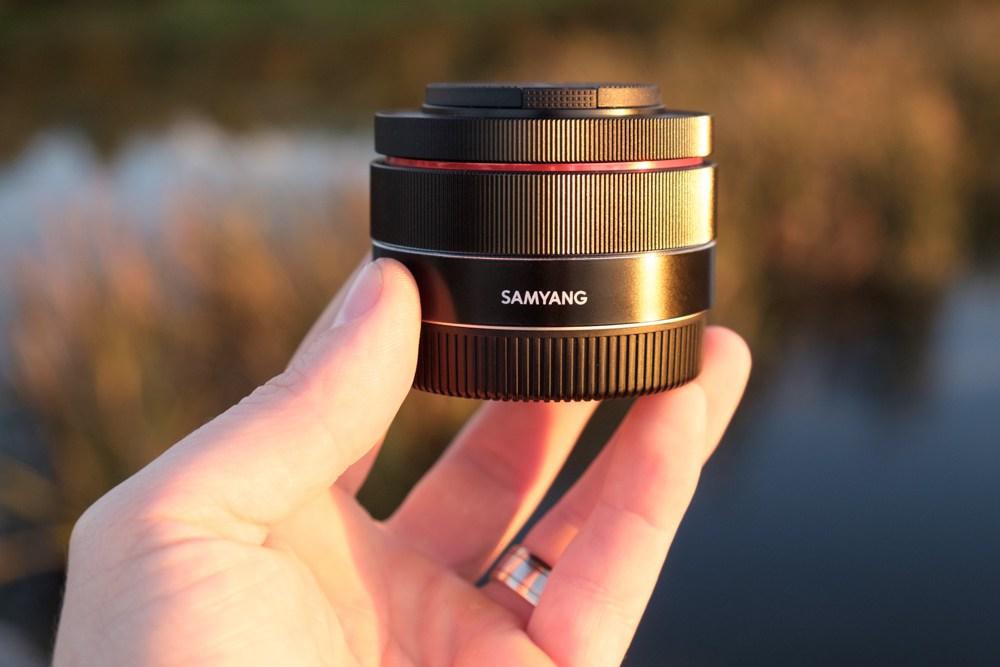 Объектив с блендой и крышкой Samyang AF 35mm f/2.8 FE в руке