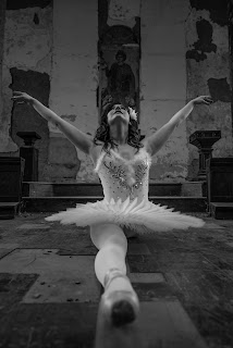 Ballerina in the splits in an abandoned building