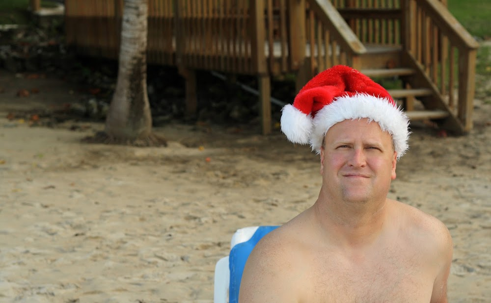man wearing christmas hat on beach