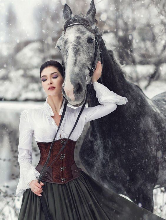 Woman wearing victorian steampunk clothing in the snow with her gray horse. Women's neo-victorian fashion and costumes.