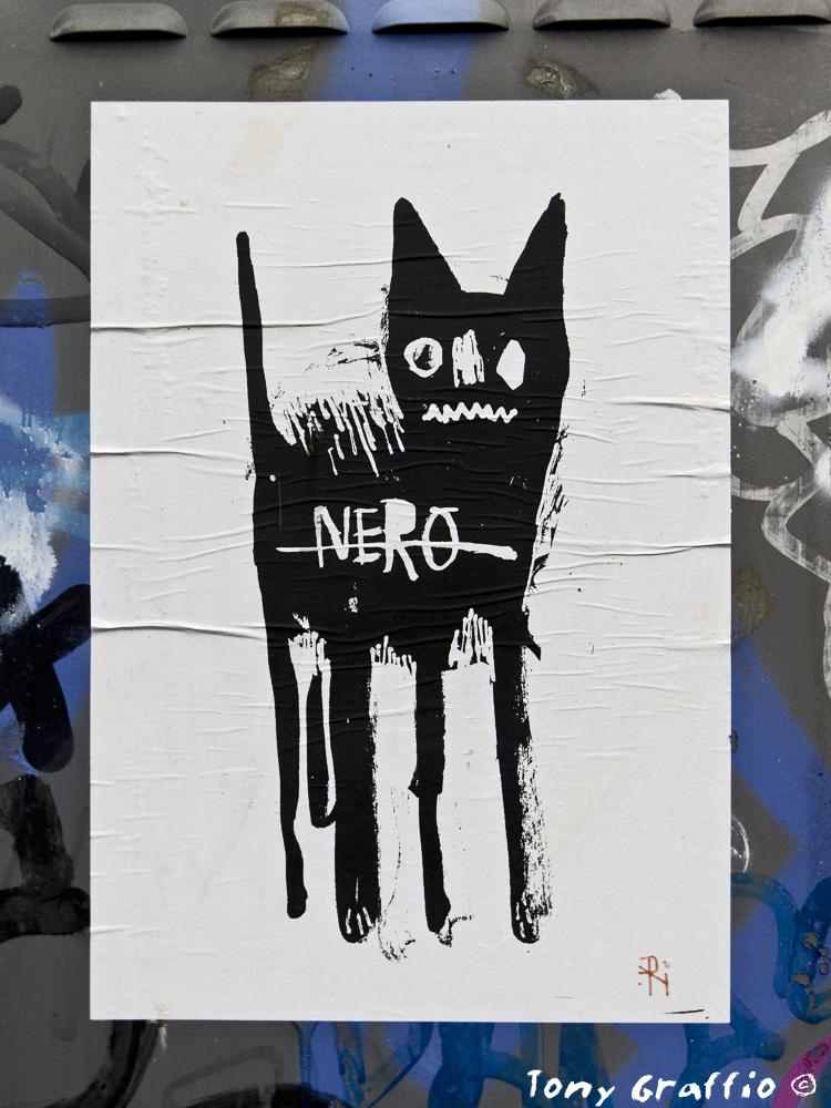Disegno di un gatto nero su un foglio appiccicato su una cabina elettrica a Milano