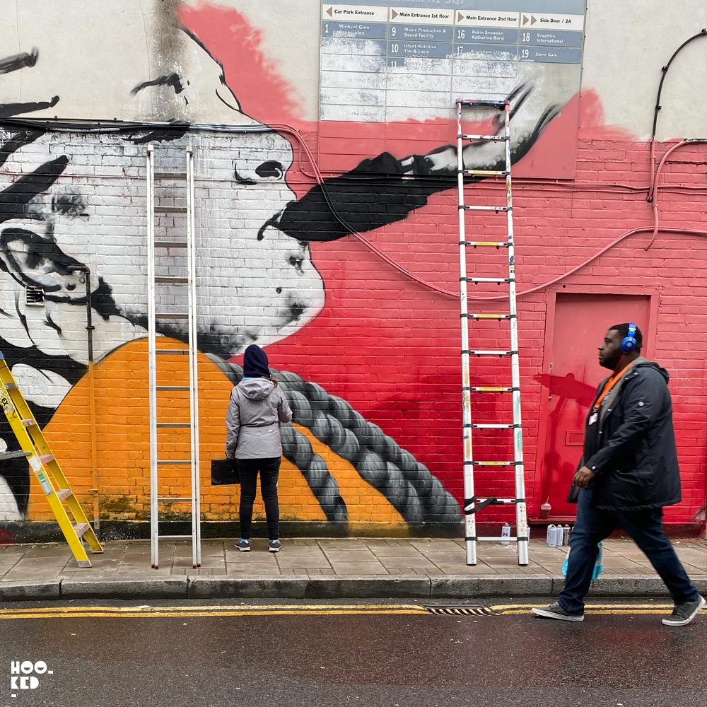 French street artist Zabou at work in the rain on her latest London mural
