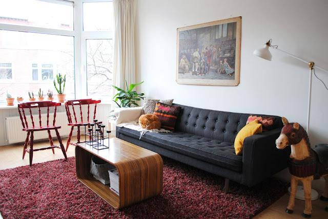 Bohemian woonkamer met stoffen Chesterfield bank, een oude schoolplaat en rode ranke houten stoeltjes.