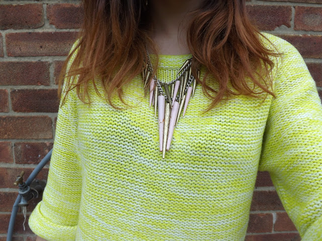 Person wearing a yellow jumper and a spiked neckalce