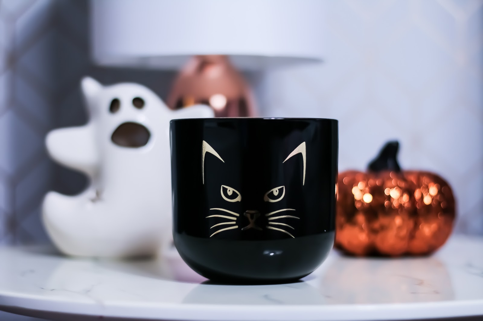 photo of a candle with a cat face on it. Black candle with white ghost candle holder in the background and a bright orange sparkly pumpkin.