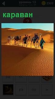 В пустыне идет караван верблюдов с погонщиками и поклажей на спинах, преодолевая песчаные холмы