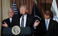 U.S. President Donald Trump speaks between Vice President Mike Pence (L) and EPA Administrator Scott Pruitt prior to signing an executive order on ''energy independence,'' eliminating Obama-era climate change regulations, during an event at the Environmental Protection Agency. (Credit: Reuters/Carlos Barria) Click to Enlarge.
