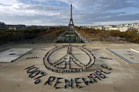 Hundreds of environmentalists arrange their bodies to form a message of hope and peace in front of the Eiffel Tower in Paris, France, December 6, 2015, as the World Climate Change Conference 2015 (COP21) continues at Le Bourget near the French capital. (Credit: Reuters/Benoit Tessier/File Photo) Click to Enlarge.
