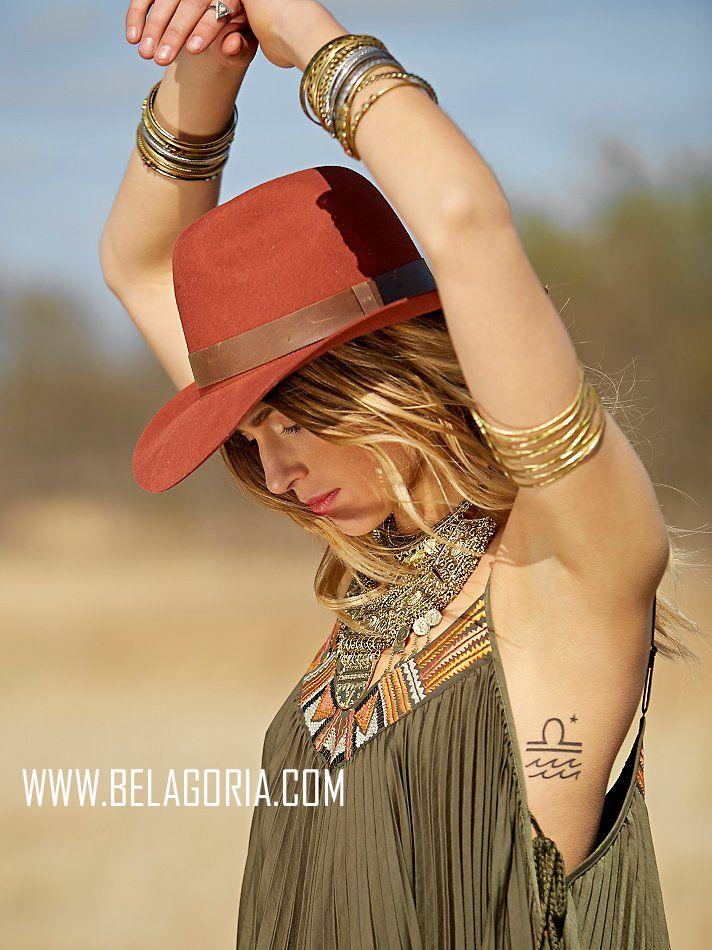 Mujer jovencita de pelo rubio con sombrero, levanta los brazos y vemos en su costillas un tatuaje de libra