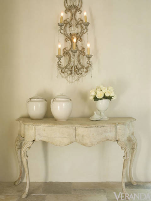 Pamela Pierce Designed vignette with oversized antique sconce, French jars, antique console table, and quiet palette.