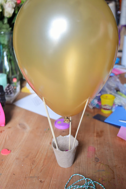 A gold balloon with skewers attached and a pot beneath.