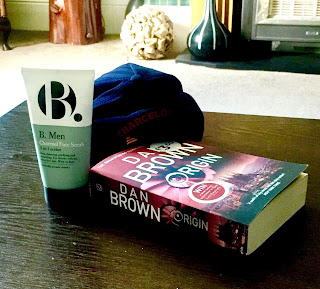 A upside down triangular bottle with a blue and white background with a big black bold b with Charcoal 3 in 1 in smaller black font next to a rectangular book saying dan brown in white font on a brown rectangular table  on a bright background