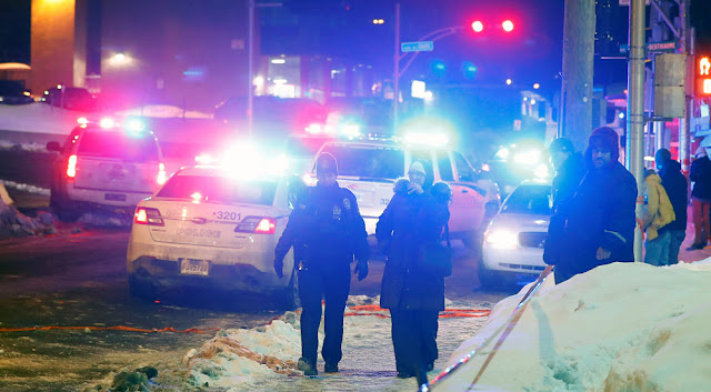 Image Attribute: Police officers are seen near a mosque after a shooting in Quebec City, January 29, 2017. REUTERS/Mathieu Belanger