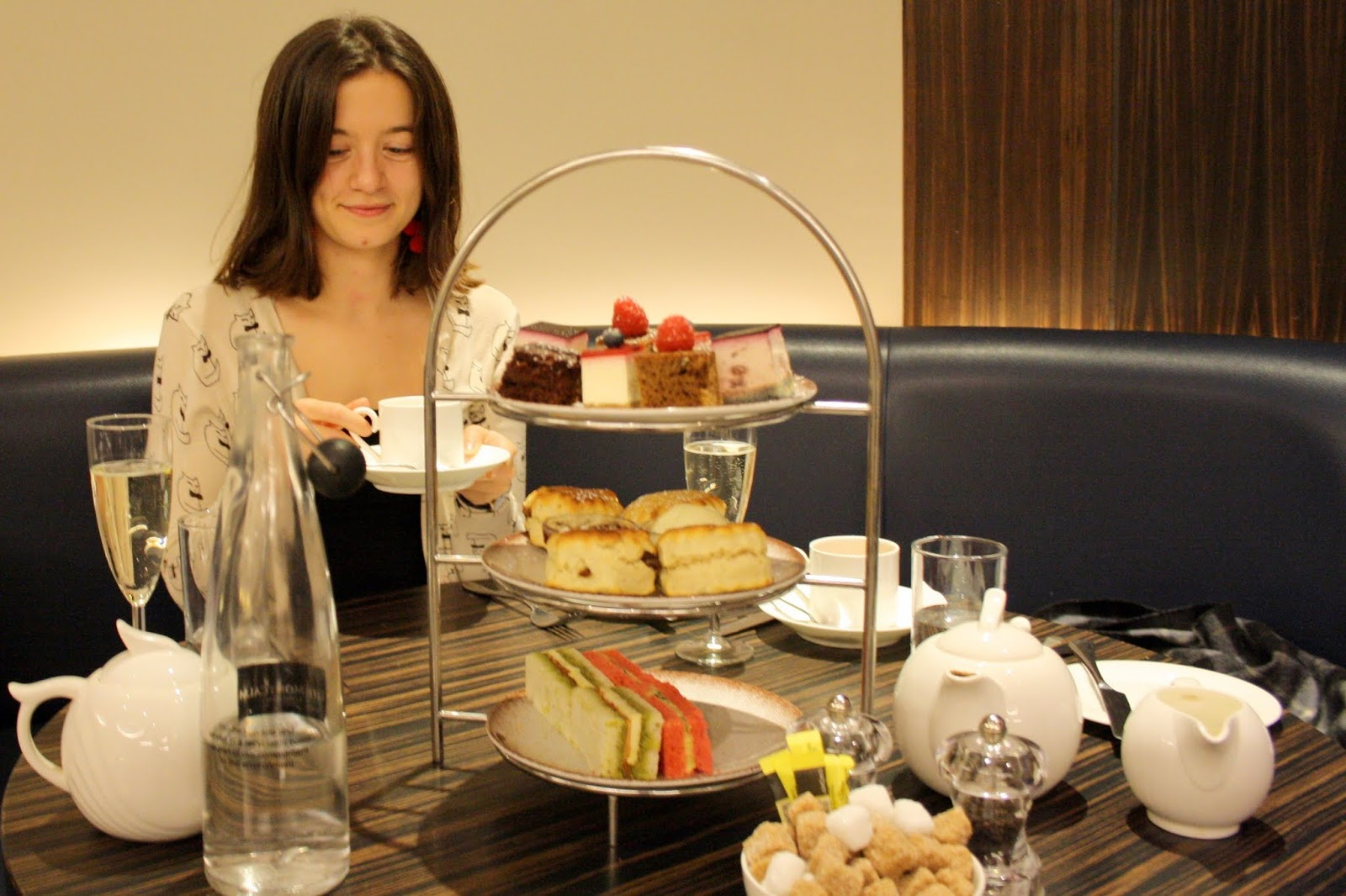 Abbey seated behind a tier of afternoon tea treats at the Montcalm Hotel, Marble Arch