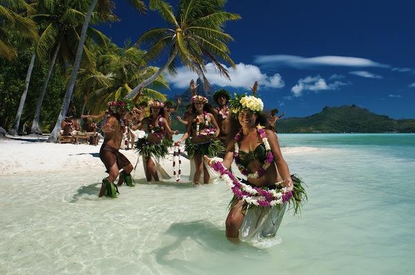 Danseuses tahitiennes avec colliers de fleurs sur la plage