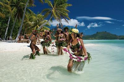 Danseuses tahitiennes avec colliers de fleurs sur la plage.