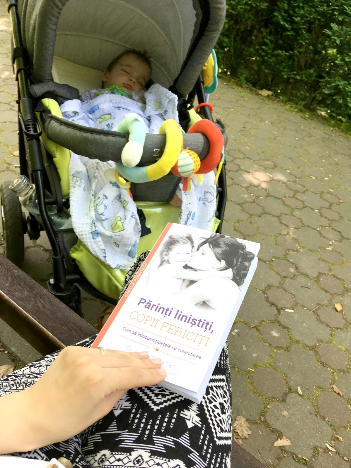 sleeping baby in stroller and mom reading parenting book