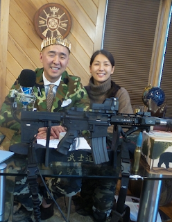 Hyung Jin Moon (Sean Moon), pictured with a crown of bullets, with his wife, Yeon Ah Lee Moon, and an AR-15 (Photo by Frances Ruth Harris)