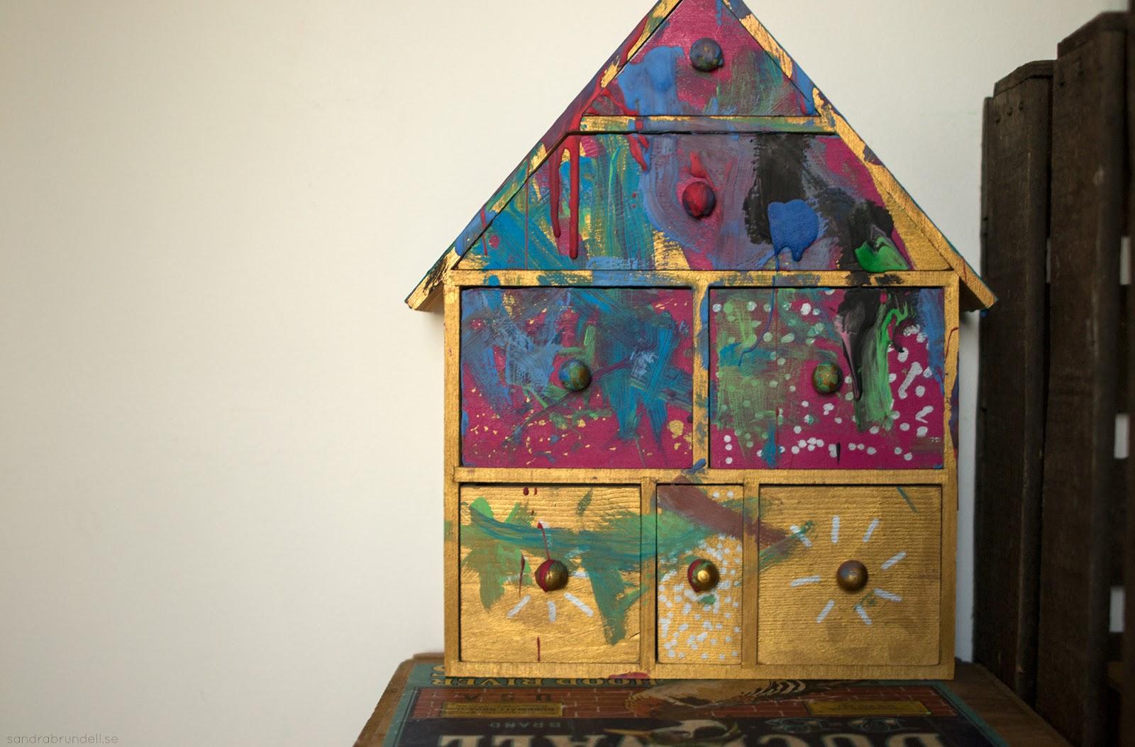 Hus med små lådor i, målat i många färger.