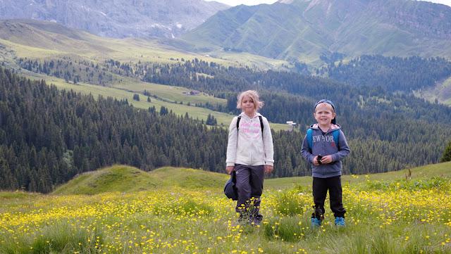 Bambini in campo di fiori con panorama dalla Alpe di Siusi