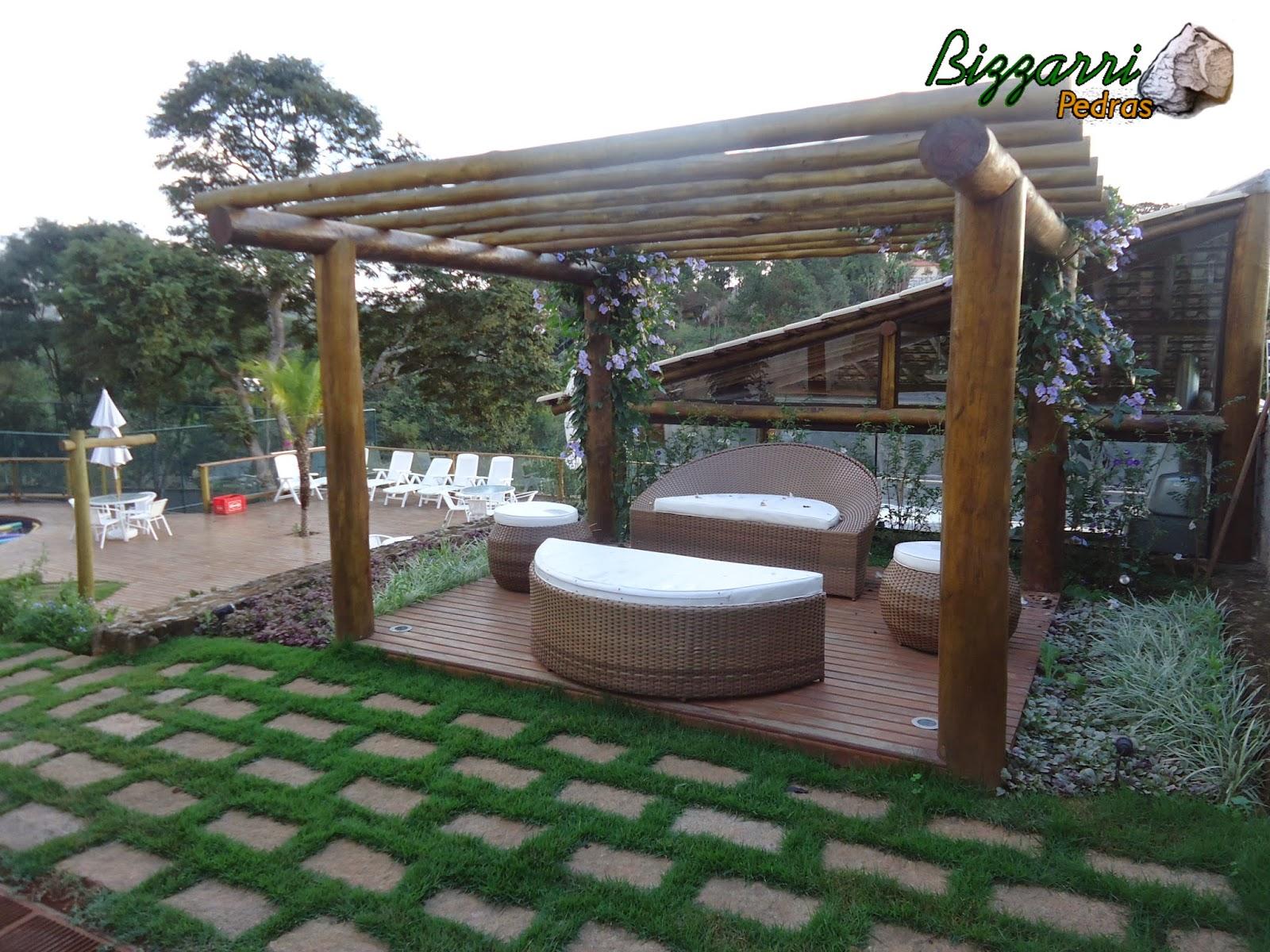 Calçamento de pedra folheta com junta de grama esmeralda em frente ao pergolado de madeira de eucalipto tratado.