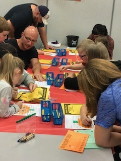 Group of parents sitting at a table working with their kids on a math activity