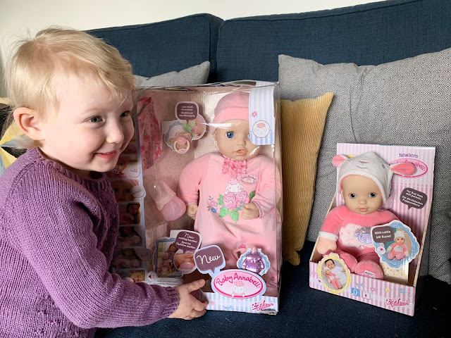 A toddler next to Baby Annabell and Baby Annabell Sweetie in their packaging ready for review
