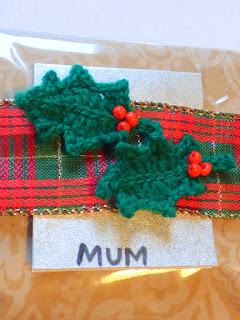 Wrapped Christmas present with crochet holly leaves