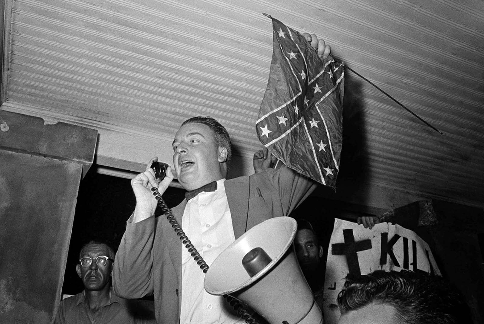 J.B. Stoner, segregationist from Atlanta, Georgia, holds a confederate flag as he addresses a large crowd of whites at a slave market in St. Augustine, Florida, on June 13, 1964 and then leads them on a long march through an African American residential section. At right is sign that read