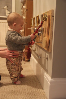 a wooden sensory board mounted on the wall with baby standing next to it
