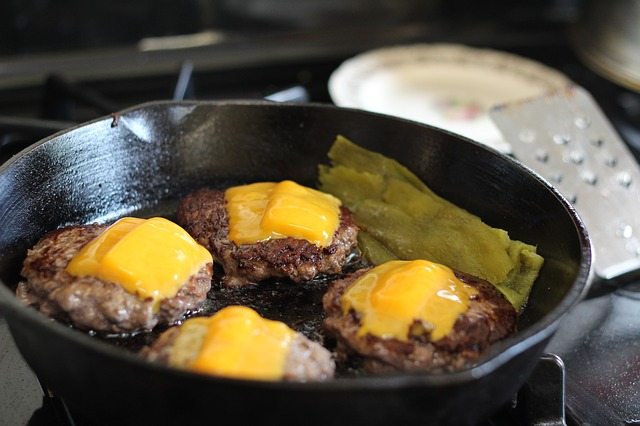 Four Hamburgers with Cheese Frying in a Cast Iron Skillet