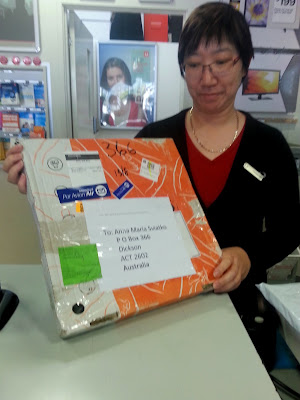 Post office assistant holding a pizza box which has been sent through the mail.