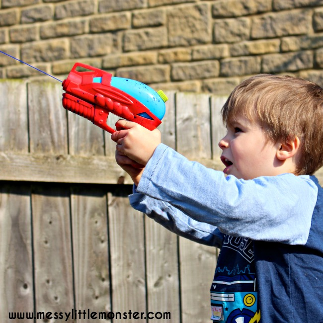 Water pistol (squirt gun) painting.  Outdoor kids art activity for Summer. Works on fine motor skills for preschoolers.