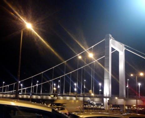 Éjszakai Budapest a kivilágított Erzsébet híd pilléreivel, Dunával és a városi forgalomban a pesti rakparton haladó csillogó tetejű autókkal.