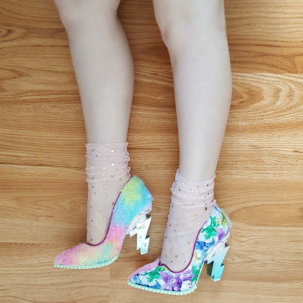 legs on floor showing side of shoes, one in rainbow pastel fur, one in unicorn print both with lightning bolt heels