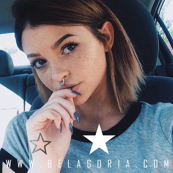 Preciosa joven tatuada en la mano con estrella