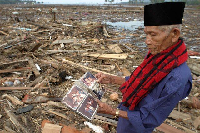Seorang Kakek memperhatikan album foto keluarganya diantara reruntuhan bangunan akibat Tsunami Aceh 2004