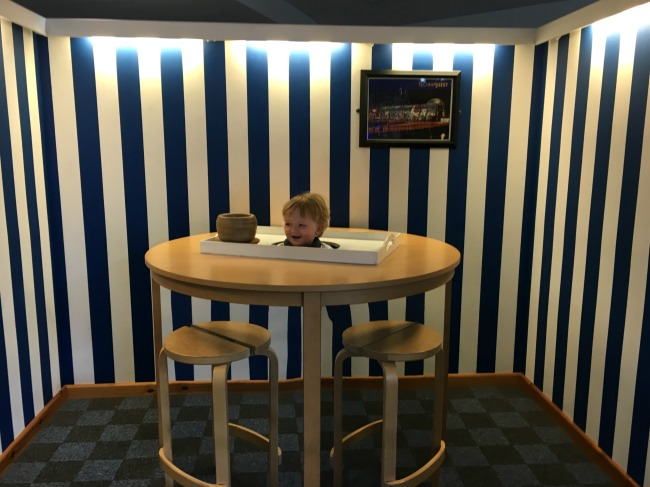 toddler-with-head-on-tray-on-table-trick-with-mirrors