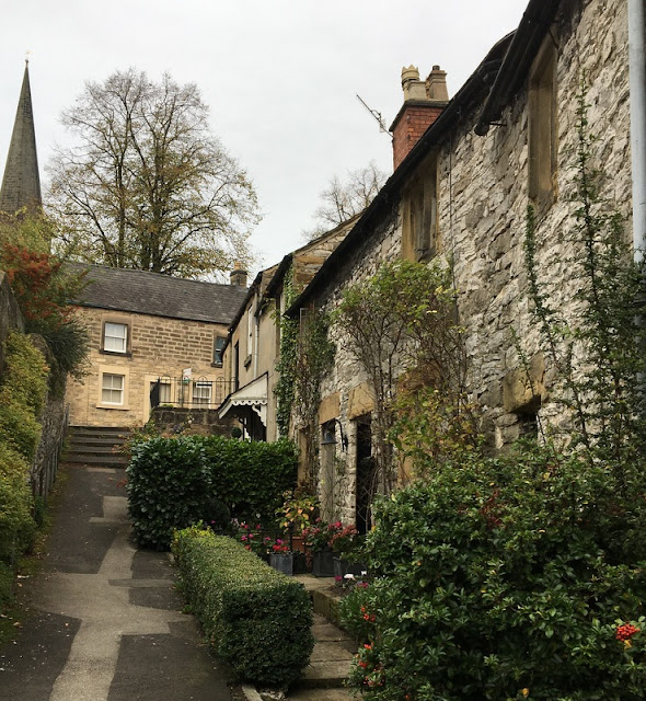 street of small stone cottages with a church spire in the distance