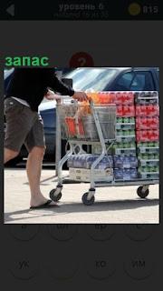К своему автомобилю на тележке мужчина везет запас продуктов