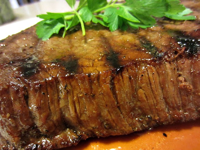 Killer London Broil by Renee's Kitchen Adventures ready to slice, still whole, on plate with parsley garnish