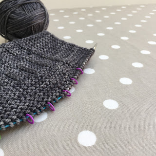 Photograph of a grey hat knitted sideways