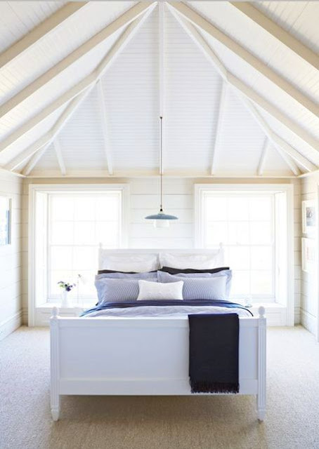 Simple, elegant bedroom with a bed with a white wooden frame and headboard, exposed beams, two windows and a single pendant light