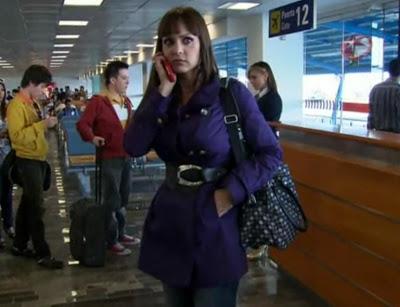 Ivana no aeroporto ao celular com casaco roxo e bolsa preta