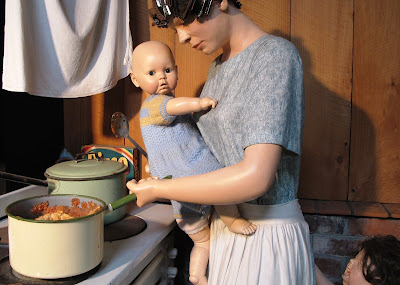Full-scale model of a 1930s woman cooking dinner, while holding a baby and having her apron tugged by a screaming child.