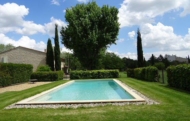 helles Farmhaus mit vielen Bäumen, Zedern, Pool, grünem Rasen
