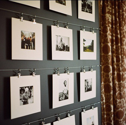 a collection of black and white photographs hanging on a metal cord