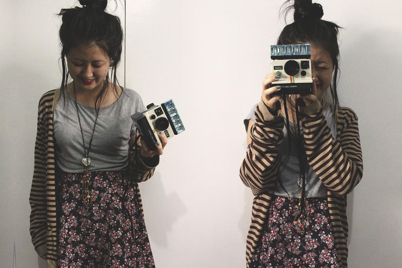 garota segurando polaroid 1000