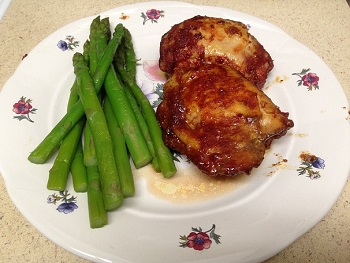 Two BBQ Chicken Thighs and a Pile of Fresh Asparagus