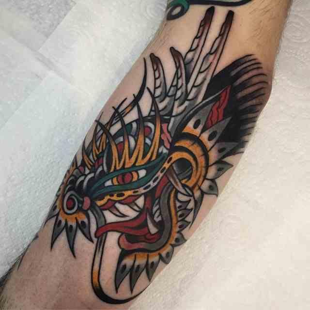 vemos a un hombre con tatuaje de dragon